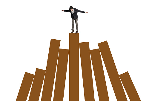 Shot of a businessman balancing on top of a graph against a white background