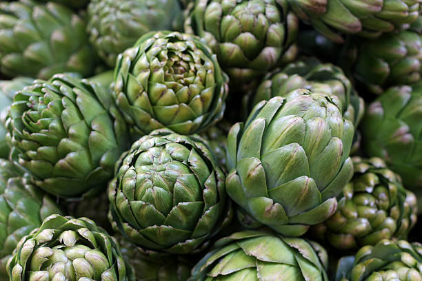 Stand of Artichokes A stand of fresh artichokes at a farmer's market with a soft background. salé morocco stock pictures, royalty-free photos & images