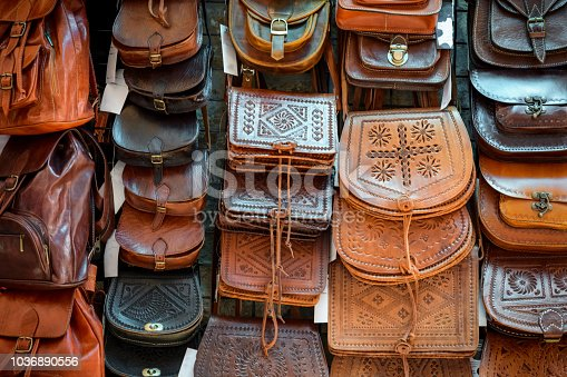 Stand on a shop full of leather bags with different color.Hand made bags