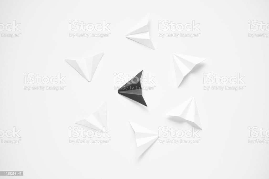 Stand out concept. Bullying concept. Black paper airplane standing...