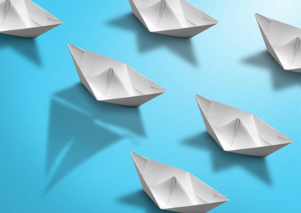 stand out concept, paper ship with sailing boat shadow on blue stock photo