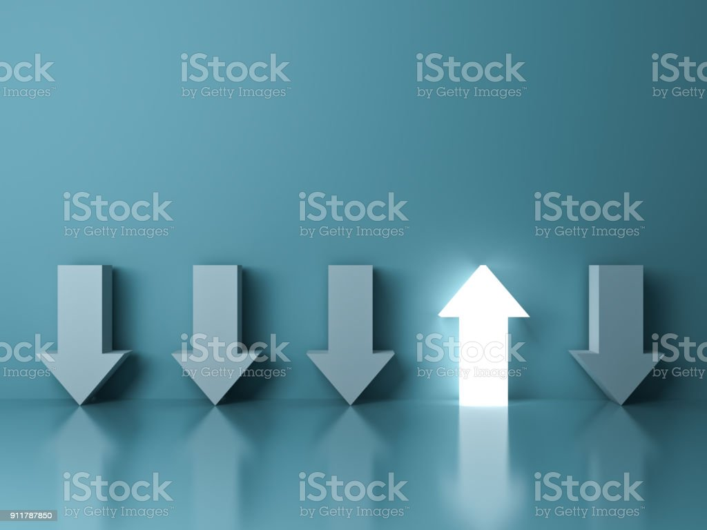 Stand out from the crowd and different concept , One glowing light up arrow among other down arrows on green pastel color background with reflections and shadows stock photo