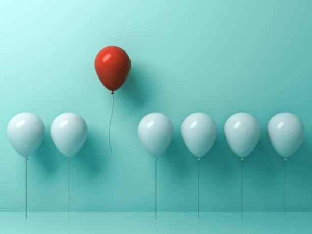 stand out from the crowd and different concept , one red balloon flying away from other white balloons on light green pastel color wall background with reflections and shadows . 3d rendering - contrasti foto e immagini stock