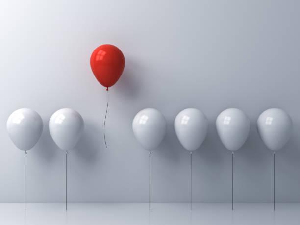 Destacam-se a multidão e conceito diferente, um balão vermelho voando longe de outros balões brancos sobre fundo de parede branca com janela reflexos e sombras. Renderização 3D - foto de acervo