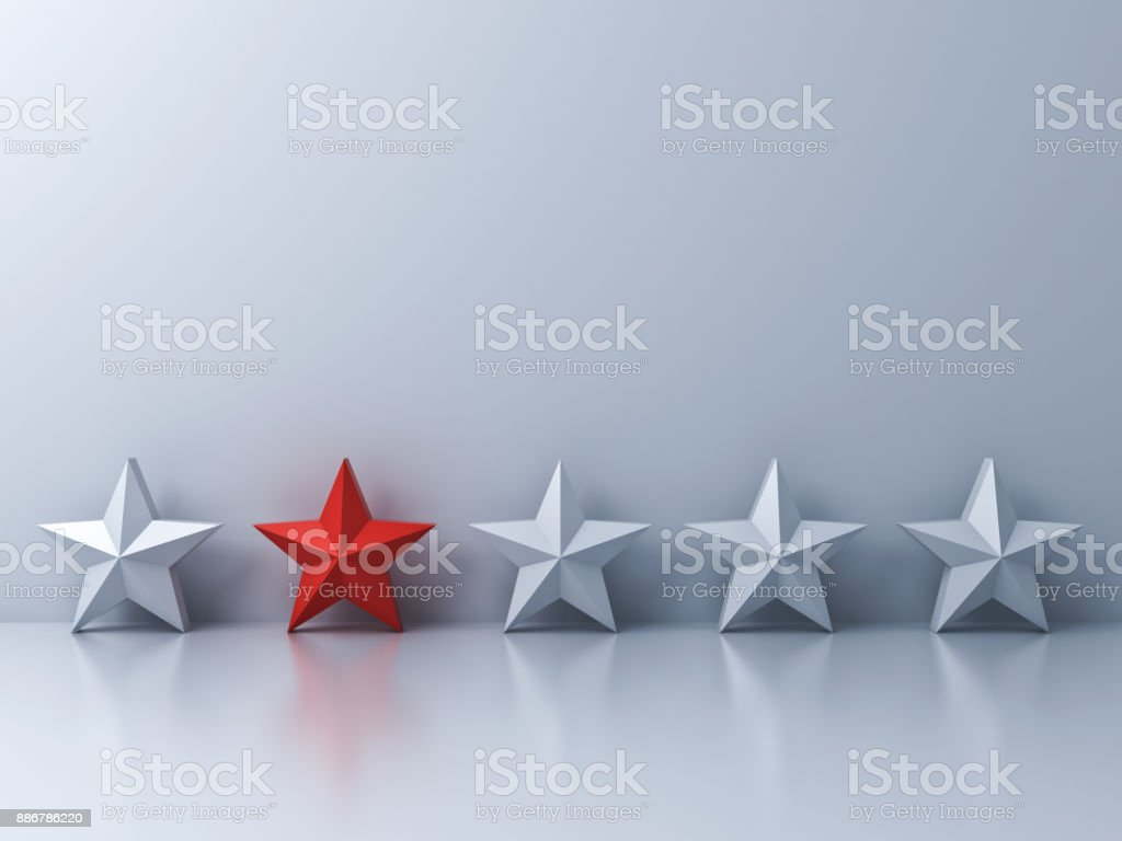 Stand out from the crowd and different concept , One red star different among white stars on white wall background with shadows and reflections stock photo