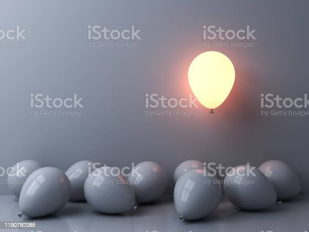 Photo of Stand out from the crowd and different concepts One light balloon glowing and floating above other white balloons on white wall background with window reflections and shadows 3D rendering
