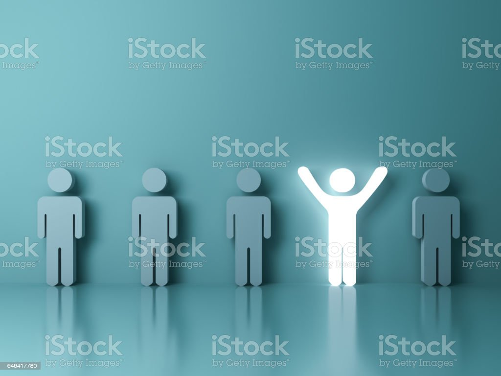 Stand out from the crowd and different creative idea concepts , One glowing light man standing with arms wide open among other people on green background stock photo