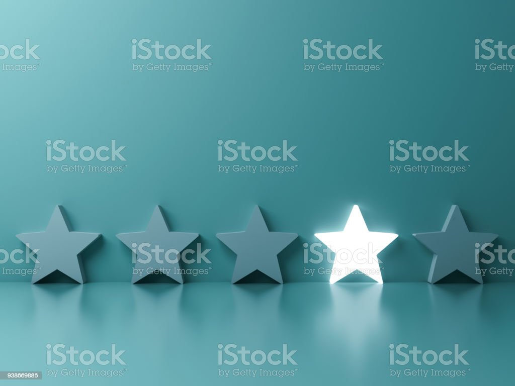 Stand out from the crowd and different creative idea concepts , One glowing star standing among other dim stars on green pastel color background with reflections and shadows stock photo