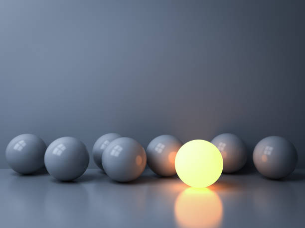 stand out from the crowd and leadership creative idea concepts one luminous sphere shining among other dim spheres on white background in the dark with reflections and shadows 3d rendering - contrasti foto e immagini stock