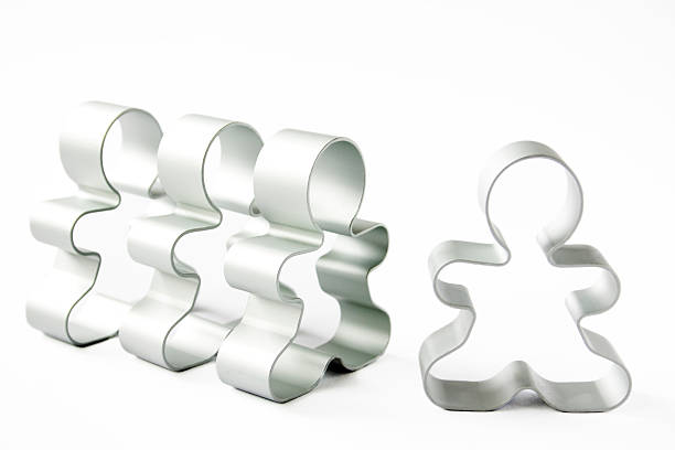 """Stand out from the Crowd """"A row of cookie cutters, with one on its own, isolated on white."""" cookie cutter stock pictures, royalty-free photos & images"""
