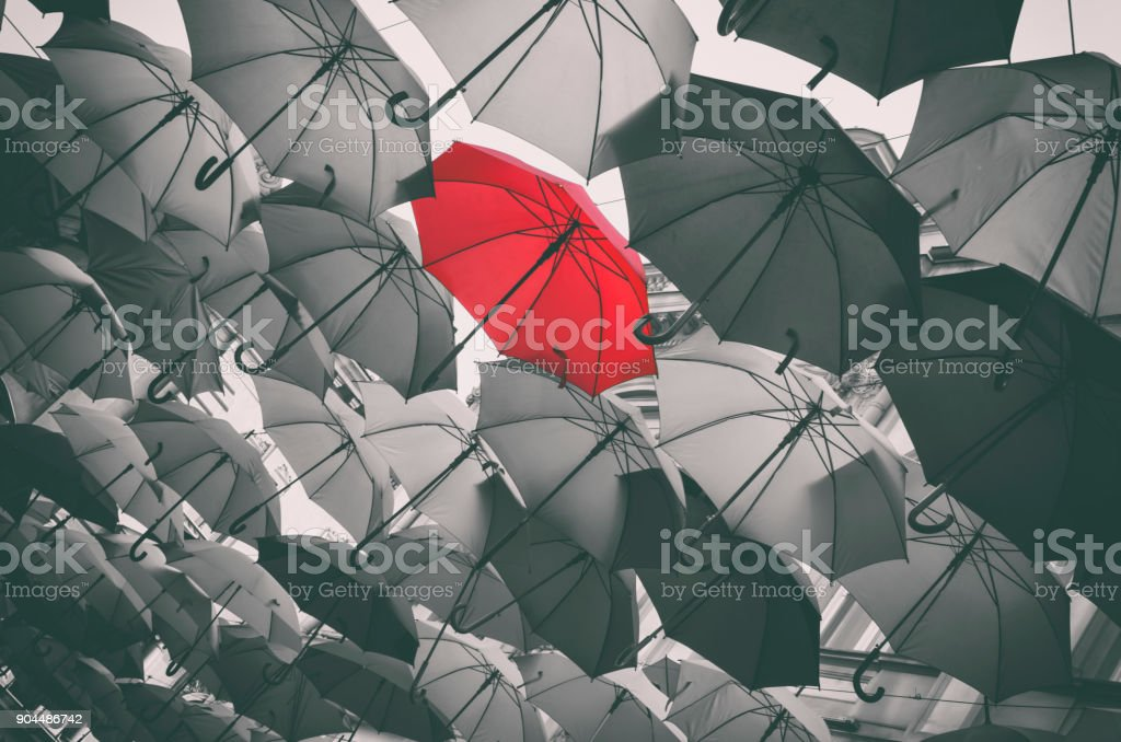 Stand out from the crowd Red different umbrella in mass of black umbrellas Autumn Stock Photo