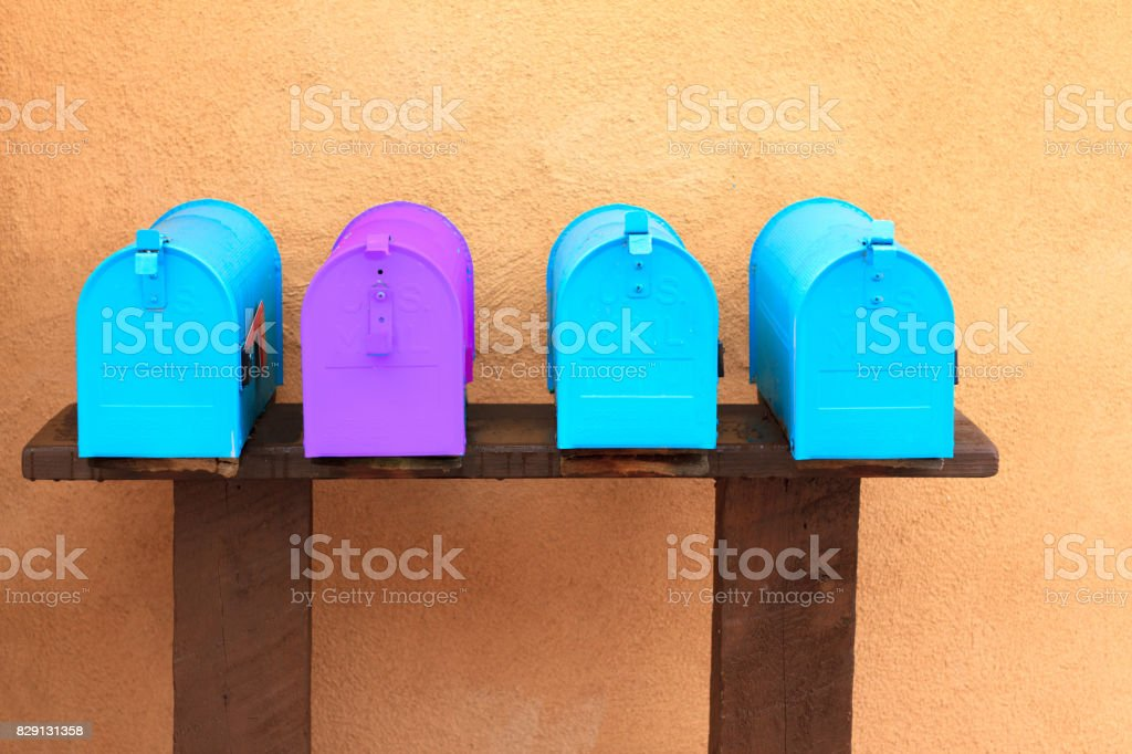 A line of rural mailboxes, with three turquoise and one purple one.
