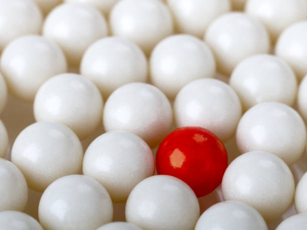 stand out red ball surrounded by white balls - cue ball stock pictures, royalty-free photos & images