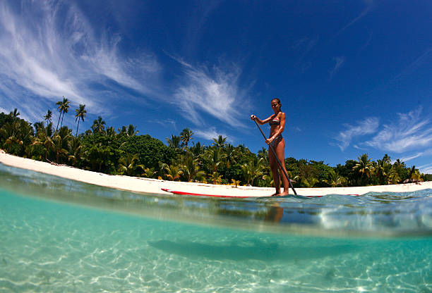stand up paddle boarding in Fiji a young woman enjoys stand-up paddle boarding in the tropical waters of Fiji south pacific ocean stock pictures, royalty-free photos & images
