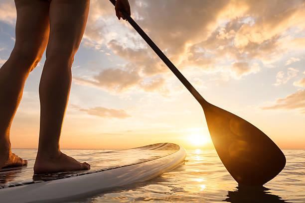 stand up paddle embarque em mar tranquilo, pernas de perto, pôr do sol - esporte aquático - fotografias e filmes do acervo