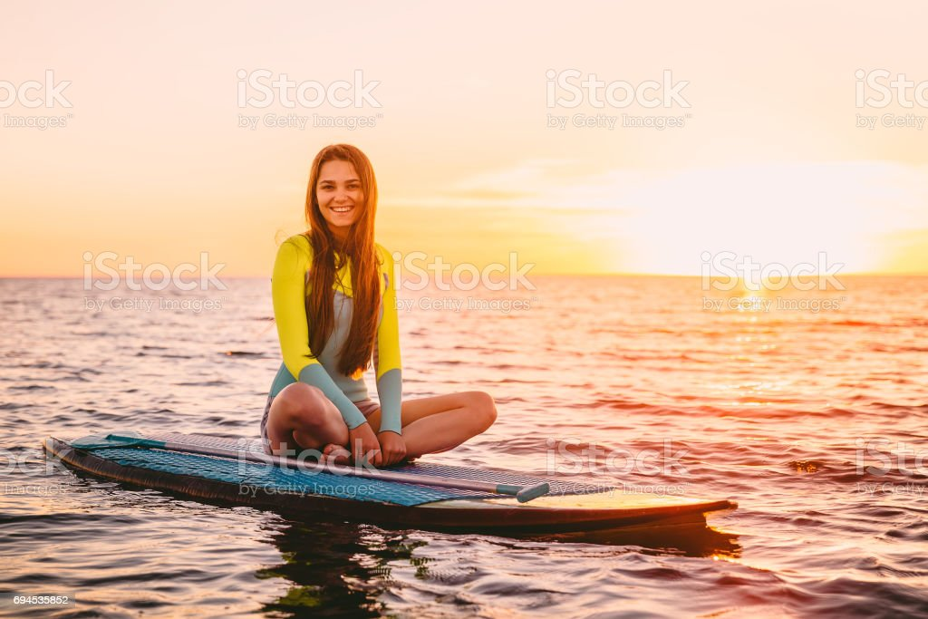 Stand up paddle boarding on sea with warm summer sunset colors. Happy smiling girl on board at sunset stock photo