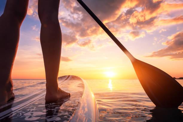 Stand Up Paddle Boarding oder Standup Paddleboarding auf ruhigem Meer bei Sonnenuntergang mit schönen Farben während des warmen Sommerstrandurlaubs, aktive Frau, Nahaufnahme von Wasseroberfläche, Beinen und Board – Foto
