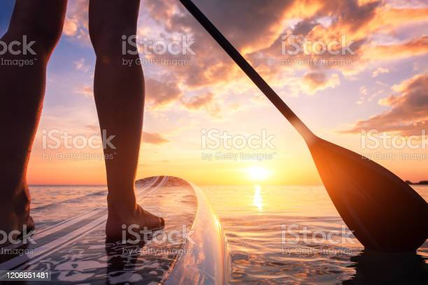 Photo of Stand up paddle boarding or standup paddleboarding on quiet sea at sunset with beautiful colors during warm summer beach vacation holiday, active woman, close-up of water surface, legs and board
