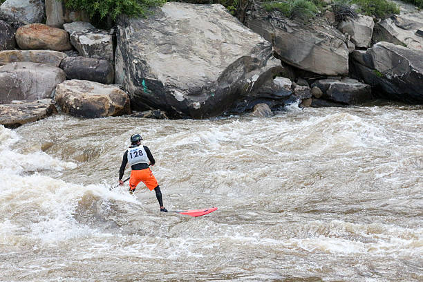 Stand up paddle boarding surf competitor #128 - Durango, Colorado Durango, Colorado, USA - May 30, 2015: A competitor in orange shorts surfs on a stand up paddle board in a river for a competition during Animas River Days in Durango, Colorado.   animas river stock pictures, royalty-free photos & images