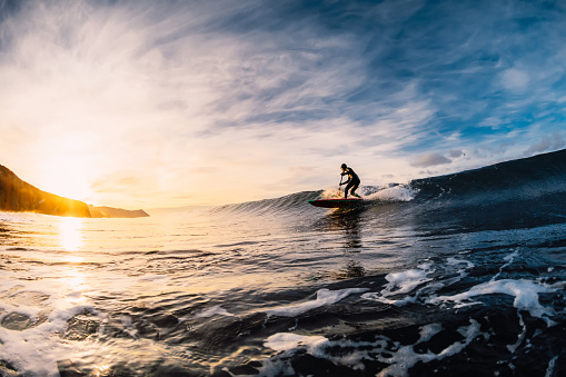 istock Stand Up Paddle surfing on waves. SUP board and surfer in wetsuit in morning 1196364041