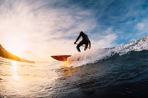 istock Stand Up Paddle surfing on waves. SUP board and surfer in wetsuit in morning 1196364089