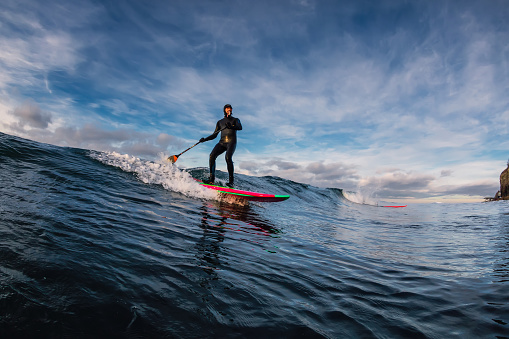 istock Stand Up Paddle surfing on waves. SUP board and surfer in wetsuit in morning 1196364176