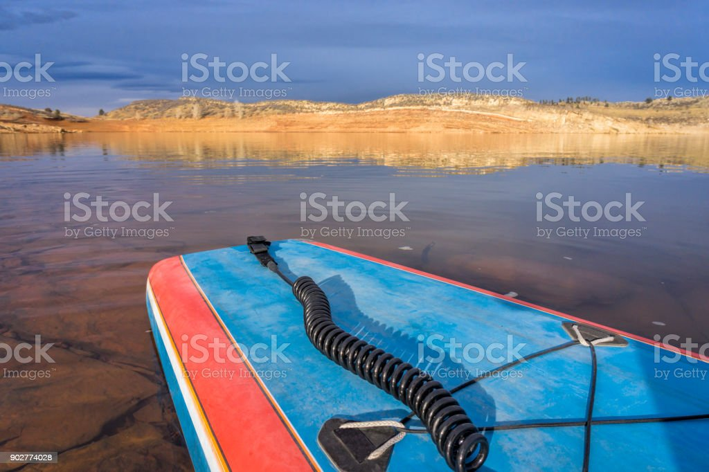 stand up paddleboard on calm  lake stock photo