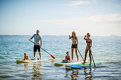 Family in Hawaii's tropical climate enjoying their vacation on stand up paddleboards (SUP) in the sea.