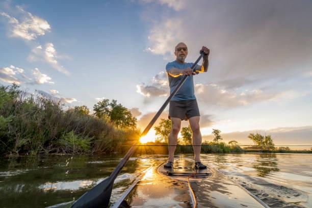 stand up paddling at sunset stock photo