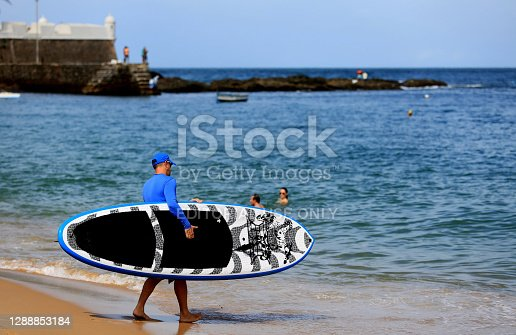 salvador, bahia, brazil - august 28, 2016: man is seen carrying a stand up board on the beach of Porto da Barra, in the city of Salvador.