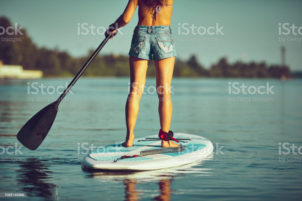 SUP Stand up Surf girl with paddle at sunset stock photo