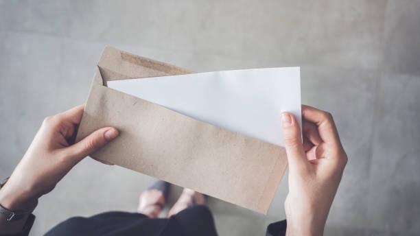 levante-se mulher segurando papel a4 dobrado branco e envelope marrom - mensagem - fotografias e filmes do acervo