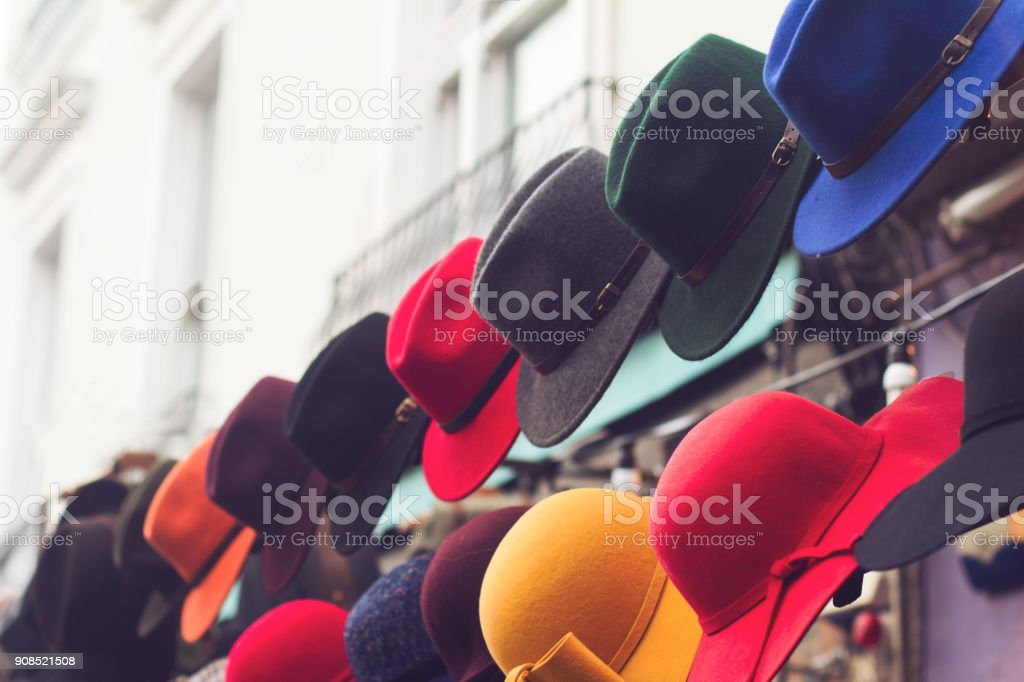 stand with colorful hats on store entrance stock photo