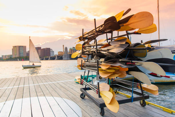 stand with paddles on a wooden pier by the river stock photo