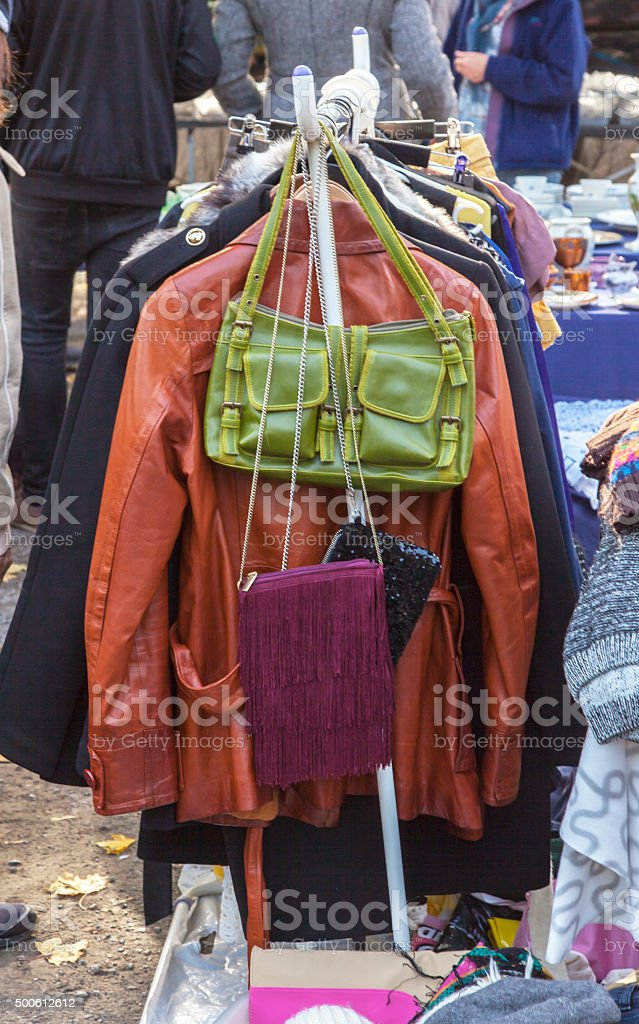 Stand with used clothing and bags at outdoor market. stock photo