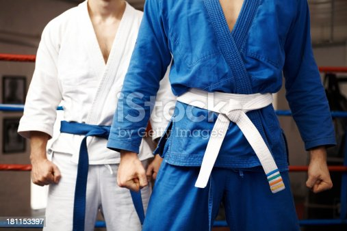 Two judo fighters stand their ground with fists ready to fight - cropped