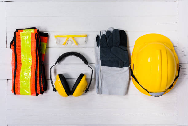 Standard construction safety equipment on wooden table. top view Standard construction safety equipment on white wooden background. top view, safety first concepts protective workwear stock pictures, royalty-free photos & images