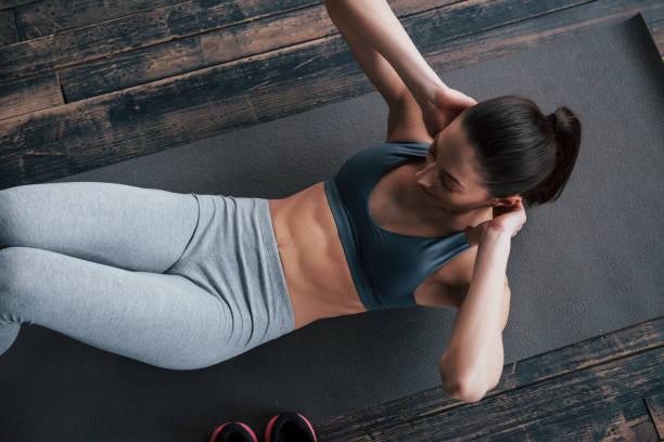 Standardübung, aber so effektiv. Top-Ansicht von Mädchen mit schlanken Körper arbeitet auf dem Bauch, wenn auf dem Boden liegen – Foto