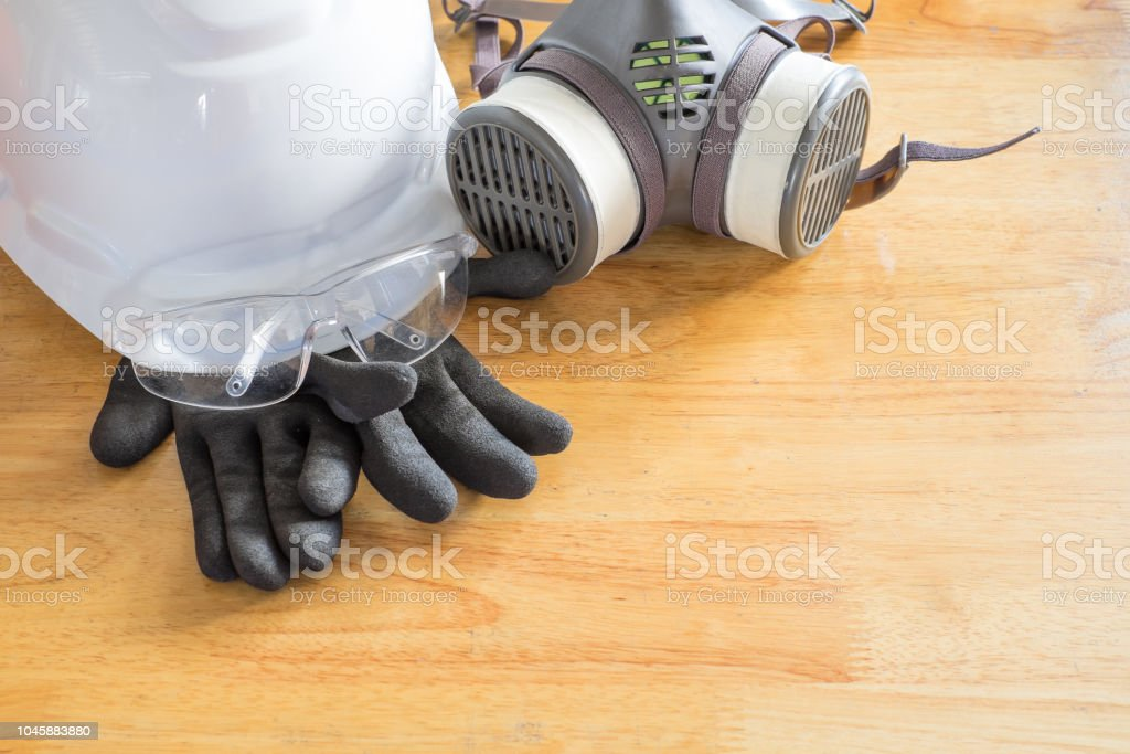 Standard personal protective equipment on wooden table. top view,...