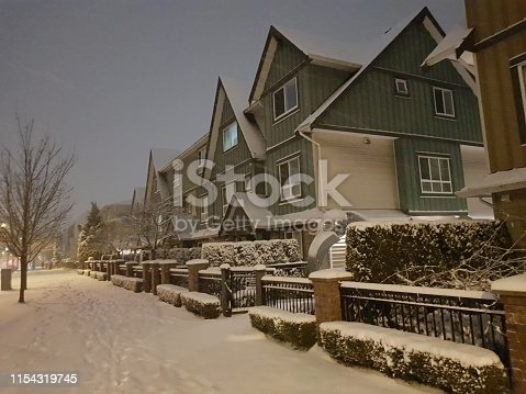 Vancouver,  BC.  Standard similar residential townhouse neighborhood.  Private residence.  No trespassing.  Winter. Snow is not removed yet.  Street lamps. Quiet night
