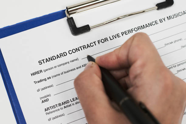 Standart contract for live performance by musicians Signing standart contract for live performance by musicians. A musician filling live performance contract muziekfestival stock pictures, royalty-free photos & images
