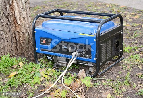 Standby Generator - Outdoor Power Equipment. Portable Generator on the House Construction Site. Close up on Home Mobile Backup Generator.