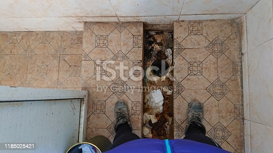 POV: Standing above a dirty squatting latrine in a smelly restroom in Tibet. Old human excrements are filling up the nasty squat latrine toilet. Traveler stands over a nightmarish public bathroom.