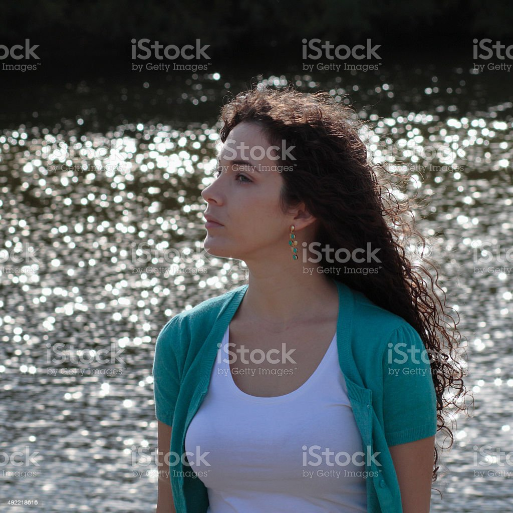 Beautiful shapely Canadian outdoor girl against sunlit water stock photo