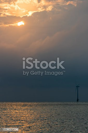 Standing against climate change. Solitary offshore wind turbine. Global warming. Single windfarm turbine at dawn or dusk with sunlight reflecting off the sea. Representing green energy initiative and enterprise.