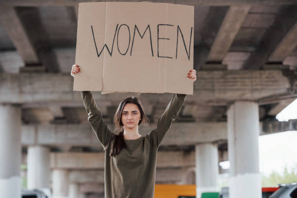 Standing alone. Pretty girl in casual clothes with handmade feminist poster in hands stock photo