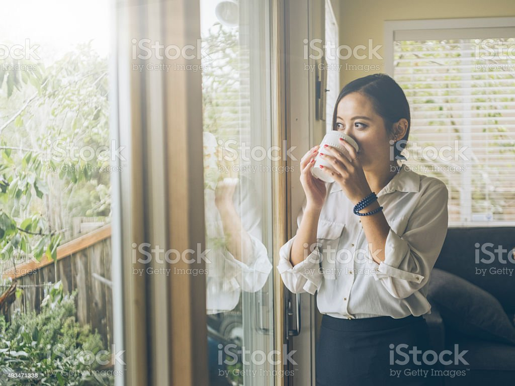 standing asian woman looking out   window at home stock photo