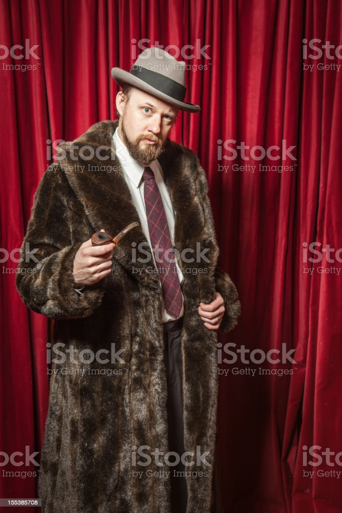 Standing Bearded Man Wearing Fedora, Fur Coat, Holding Pipe royalty-free stock photo