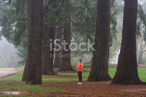 A fit Caucasian mid-adult female standing between thick tree trunks checking her smartwatch with a water bottle with copy space Portland Oregon USA