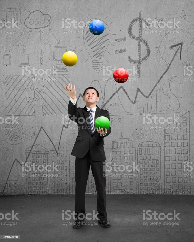 standing businessman playing colorful balls stock photo